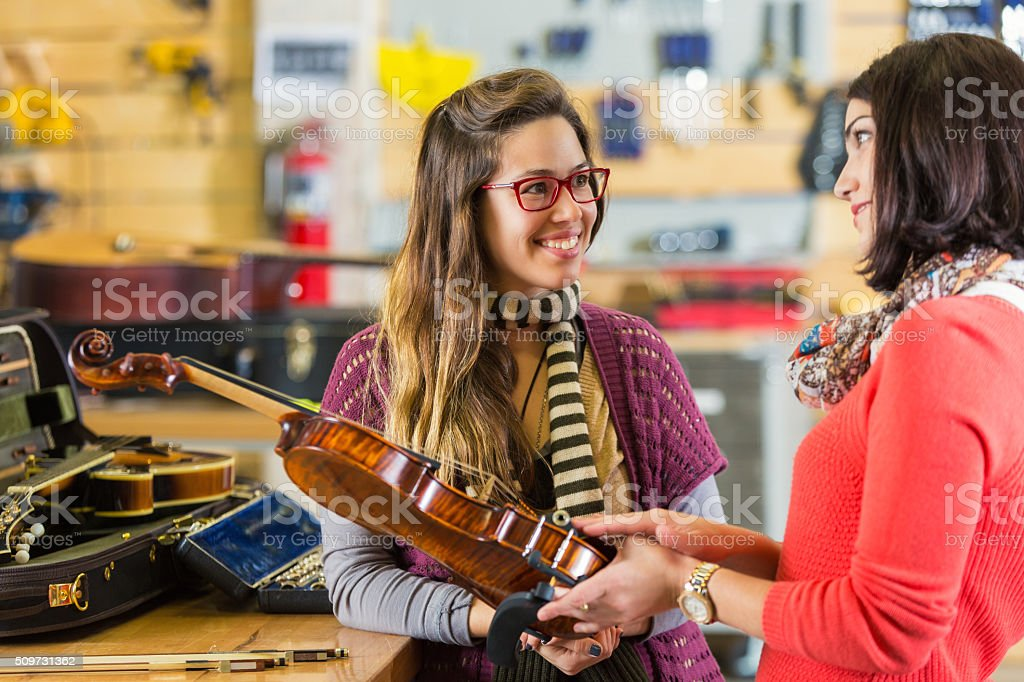 Woman talks to music store employee about violin stock photo