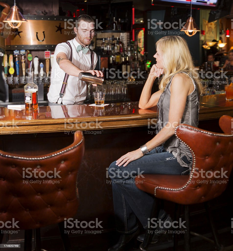 Woman talks with the bartender while he mixes drinks royalty-free stock photo