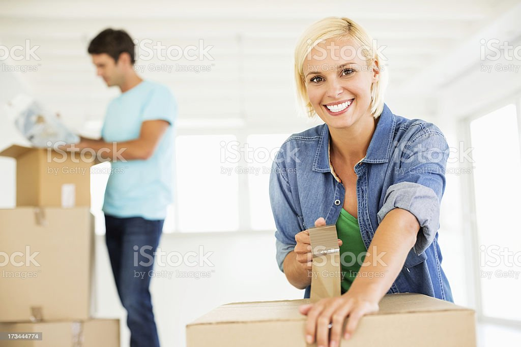 Woman Taping Cardboard Box With Man In Background royalty-free stock photo