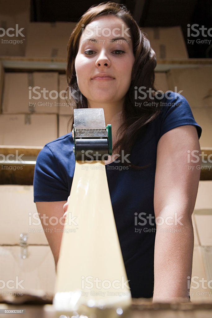 Woman taping up box stock photo
