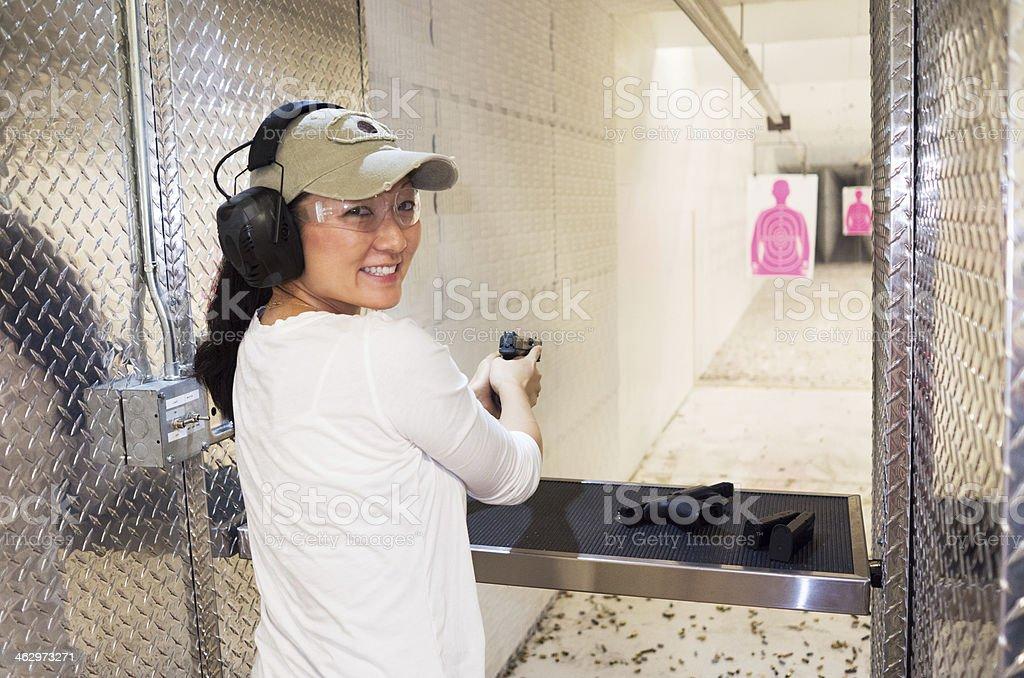 Woman target shooting with handgun stock photo