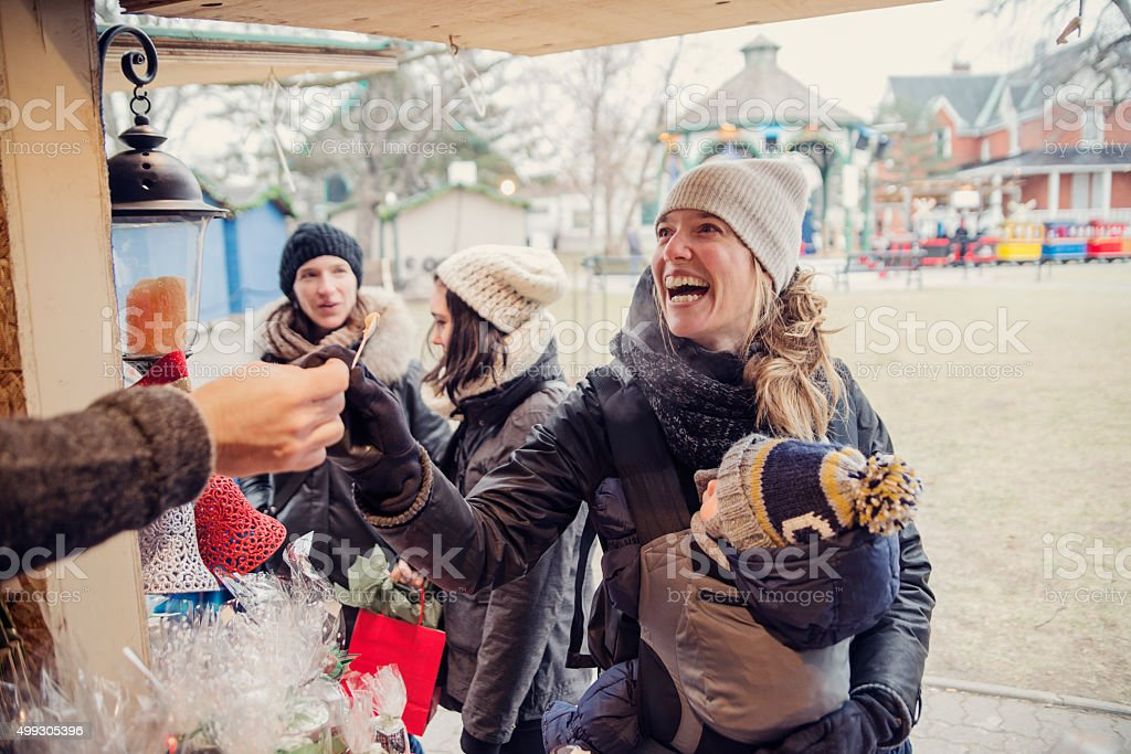Woman tasting product at an outdoors public market in winter. stock photo