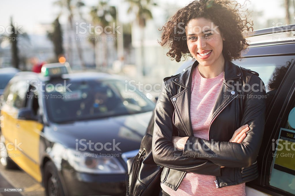Woman taxi driver next to her car. stock photo