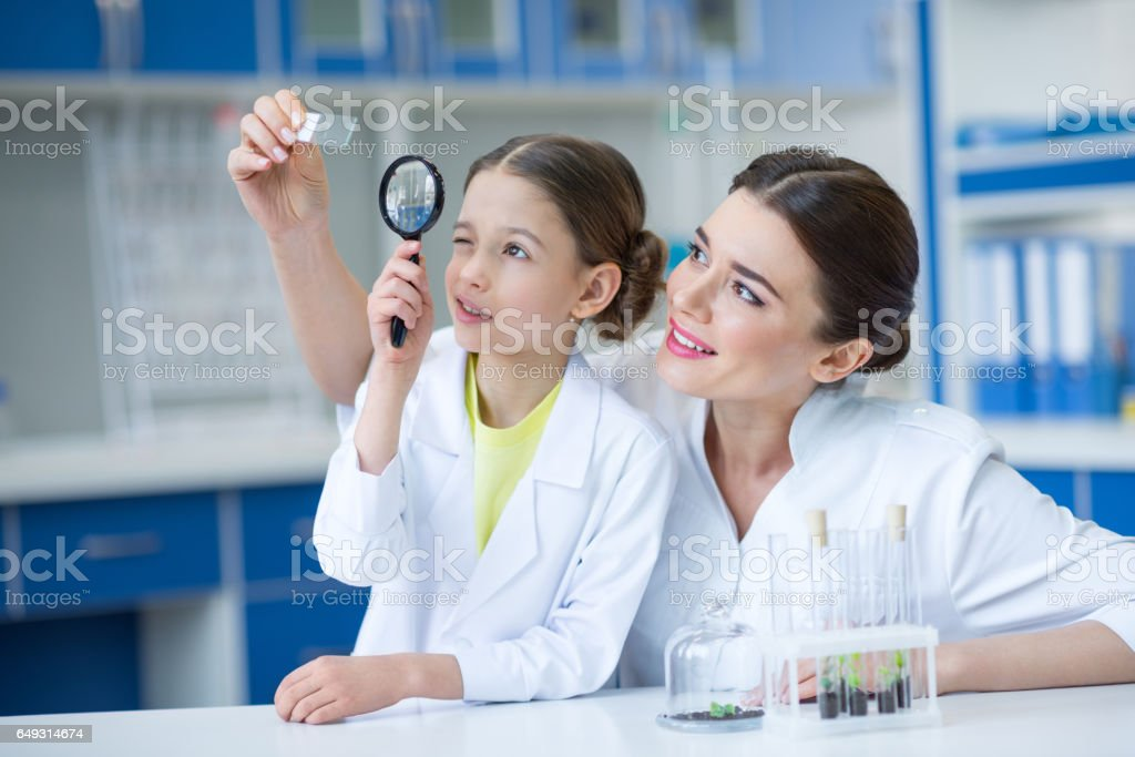 Woman teacher and girl student scientists looking at glass microscope slide through magnifier stock photo