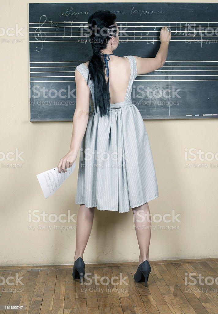 Woman Teacher Writing at Blackboard stock photo