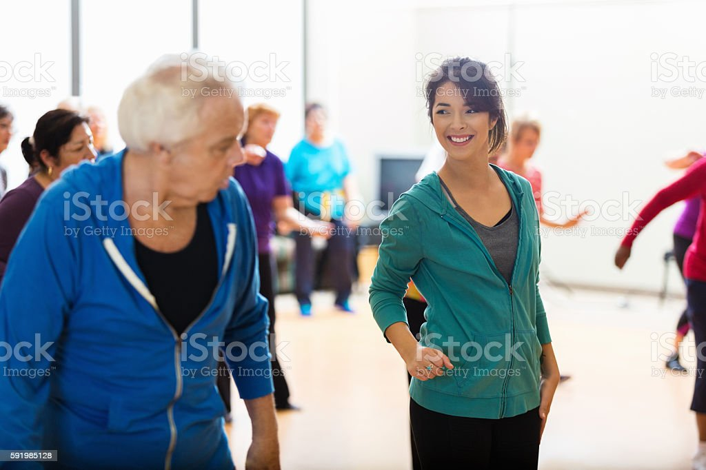 Young female dance instructor teaches senior man to line dance....
