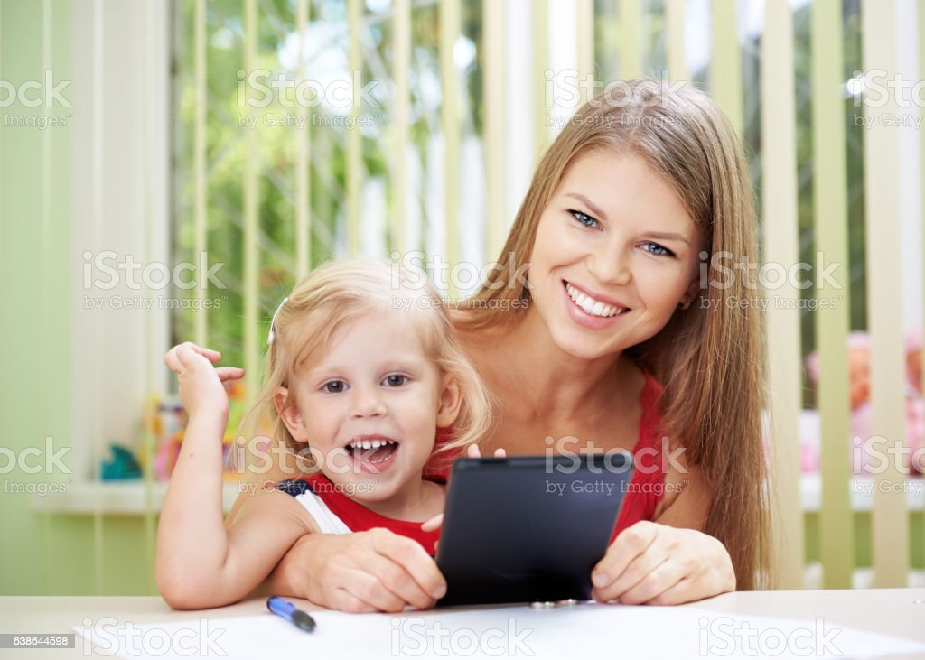 Woman teaching child with tablet pc stock photo