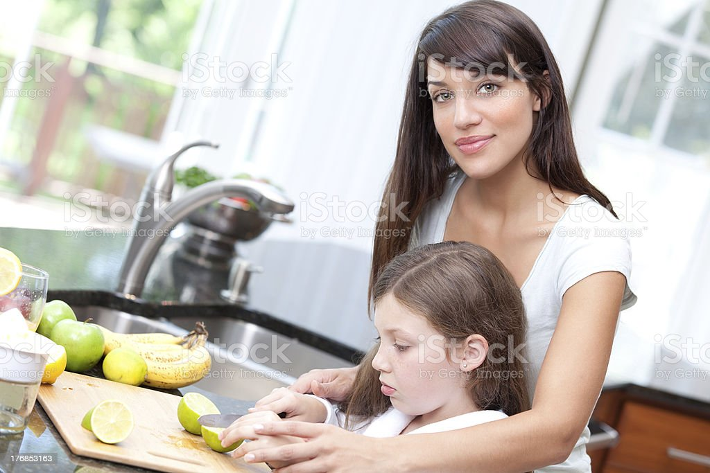 Woman teaching daughter kitchen safety royalty-free stock photo