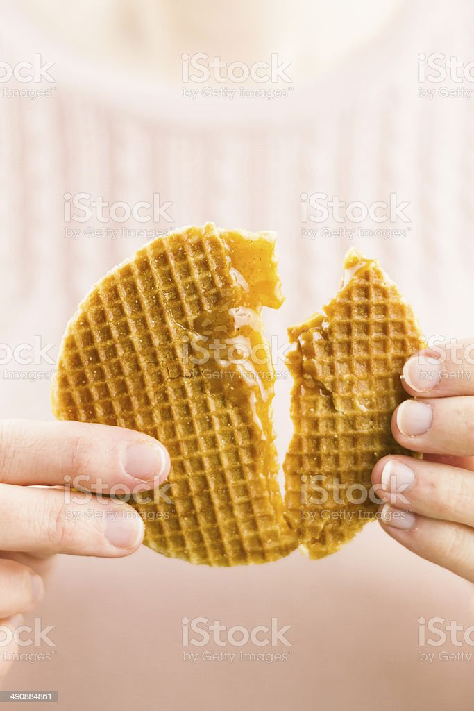 Woman tearing a dutch syrup waffle royalty-free stock photo