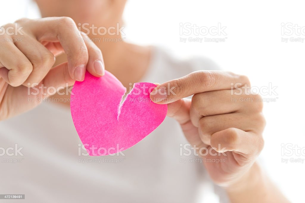 Woman tearing pink heart-shaped paper stock photo