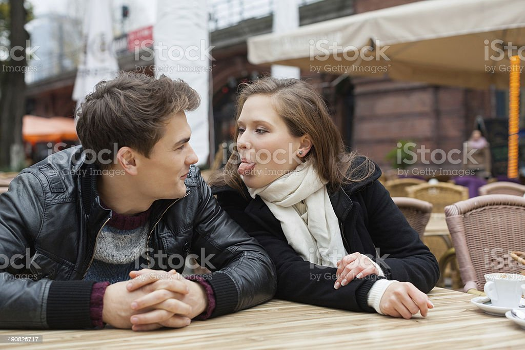 Woman Teasing Man While Sitting At Outdoor Restaurant stock photo