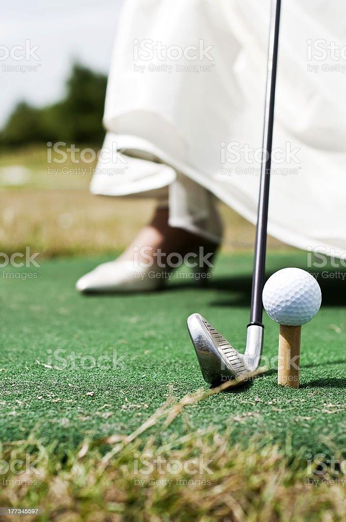 Woman teeing off golf ball on high heel wedding dress royalty-free stock photo