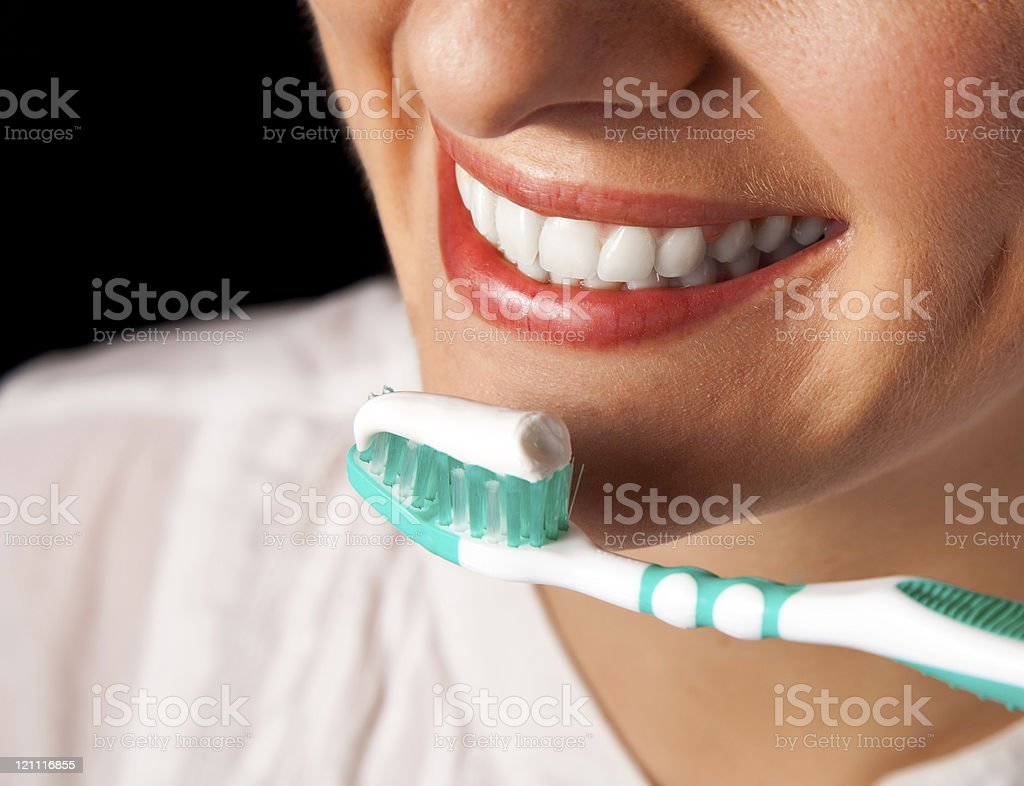 Woman teeth cleaning on black background royalty-free stock photo