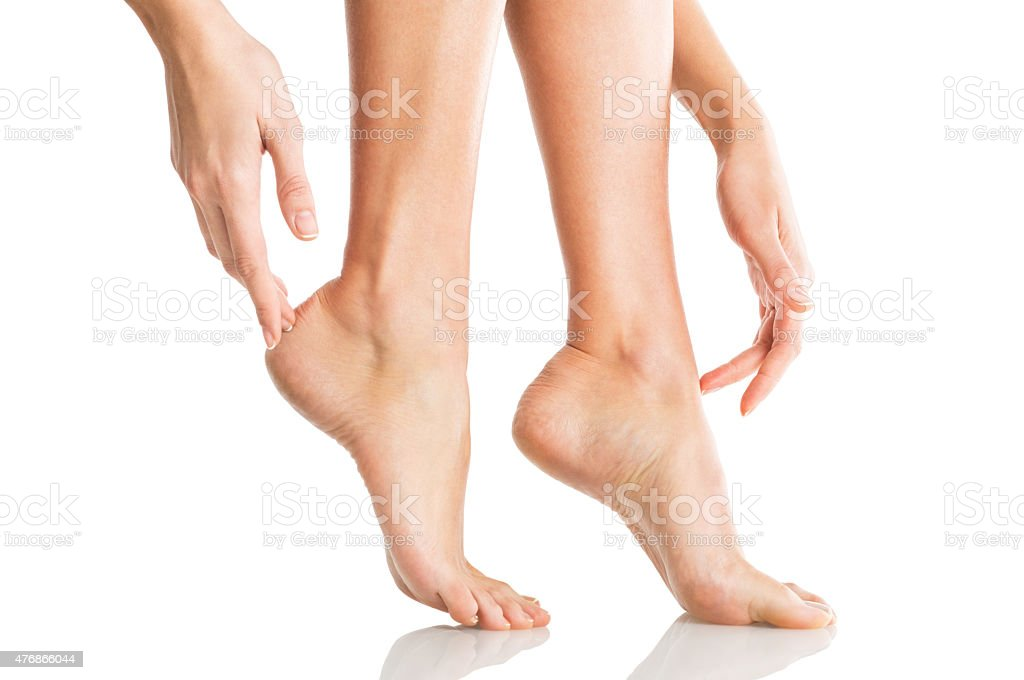 Woman tenderly touches her feet stock photo