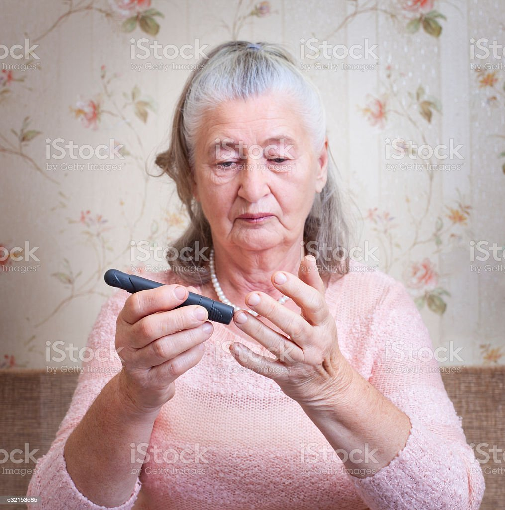 Woman testing for high blood sugar. stock photo