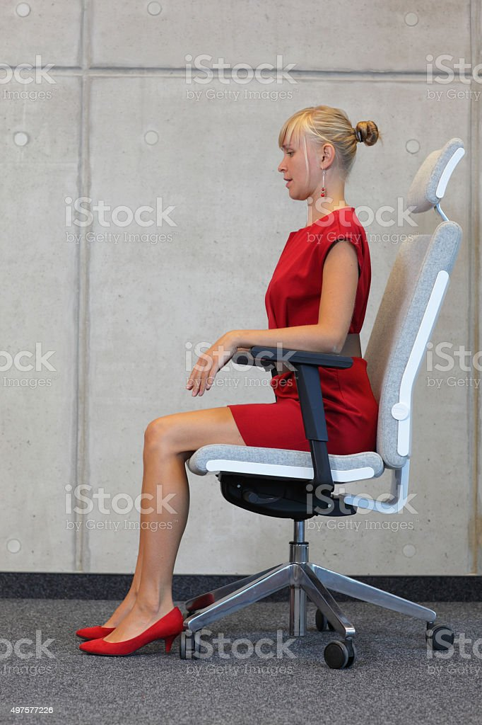 Woman testing office chair making herself comfortable stock photo