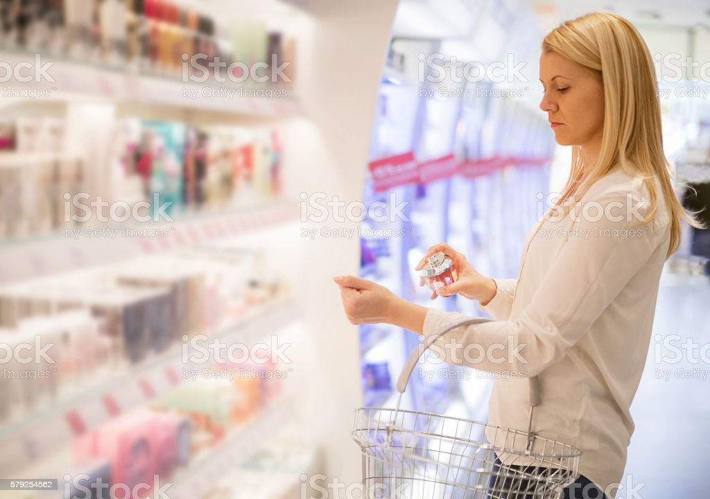 Woman testing parfume in store stock photo