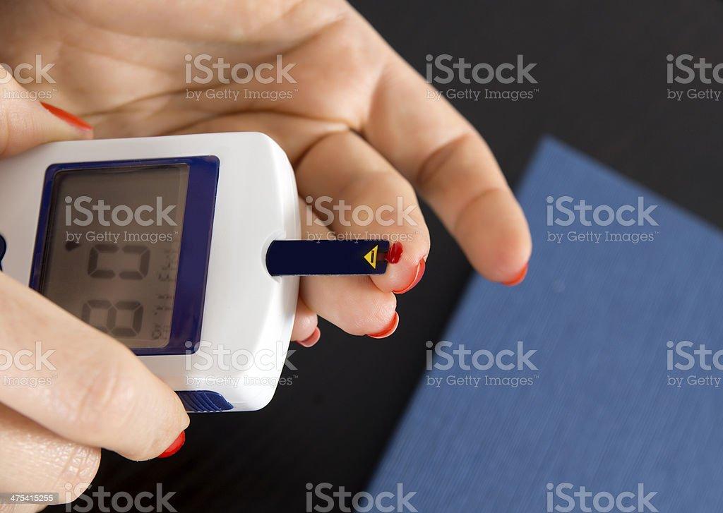 Woman Tests Blood Sugar stock photo