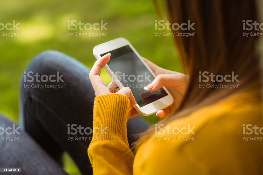 Woman text messaging in park stock photo