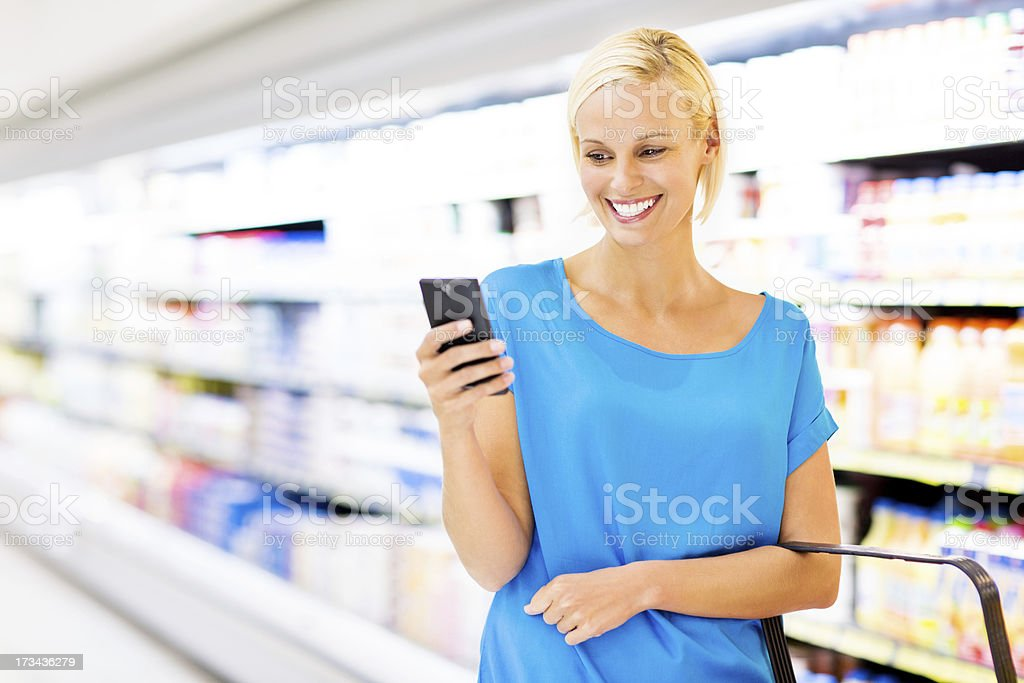 Woman Text Messaging On Smart Phone While Shopping In Store royalty-free stock photo