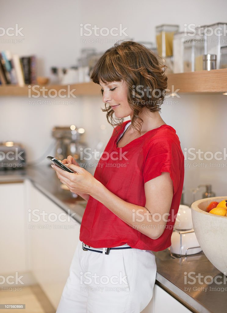 Woman text messaging while she is in the kitchen royalty-free stock photo