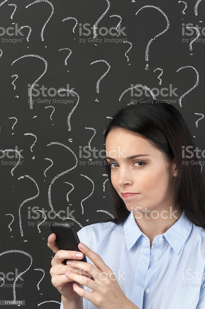 Woman Texting Against Black Background with Question Marks royalty-free stock photo