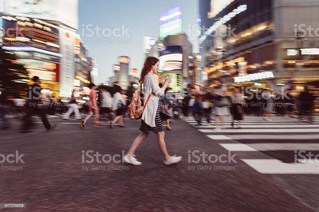 Woman texting at Shibuya crossing stock photo