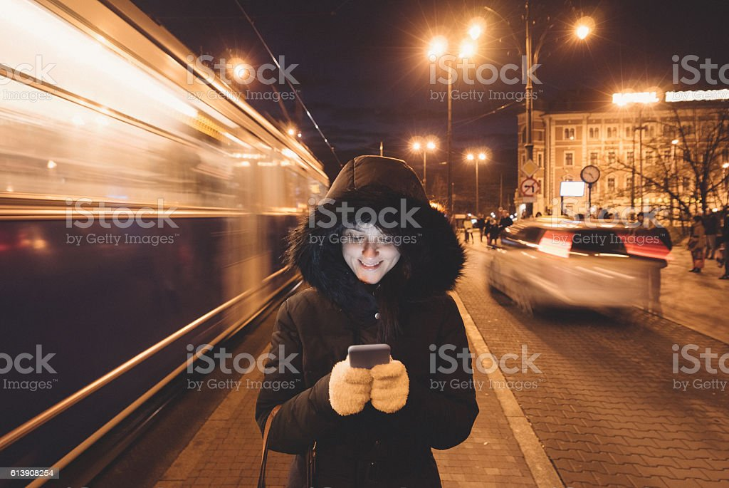 Woman texting at the bus stop stock photo