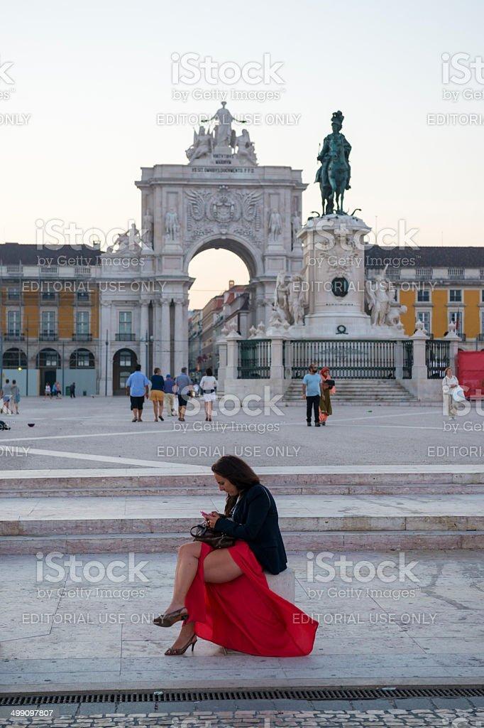 Woman texting in Lisbon's Pra?a do Com?rcio stock photo