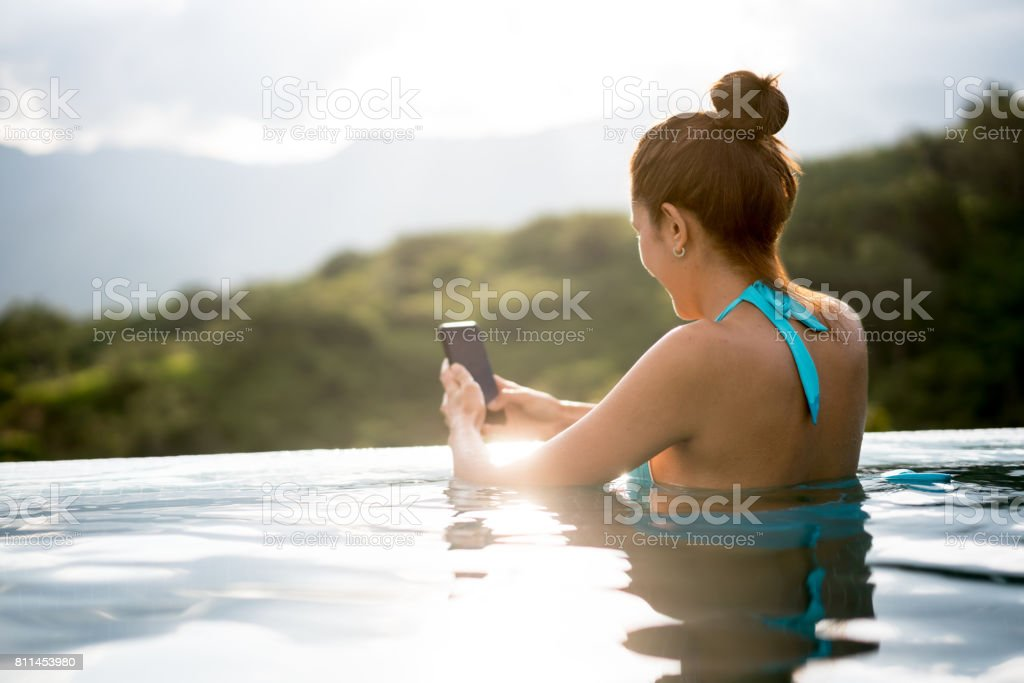 Woman texting in the swimming pool while relaxing stock photo