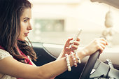 Woman texting on a cell phone in her car