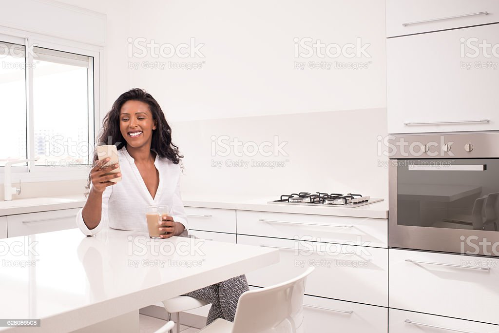 Woman texting on cell phone, sitting at white kitchen. stock photo