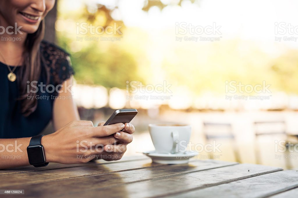 Woman texting on her smartphone stock photo