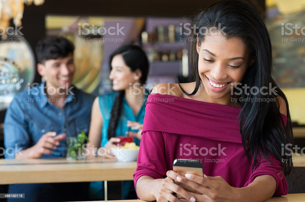 Woman texting on phone at coffee bar stock photo