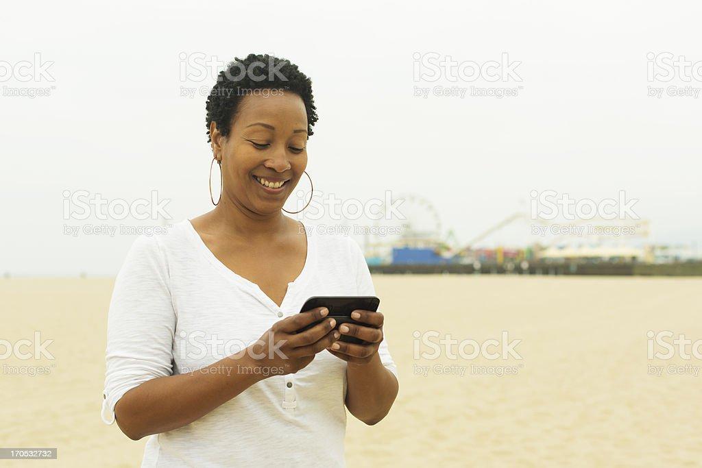 Woman Texting on Santa Monica Beach royalty-free stock photo