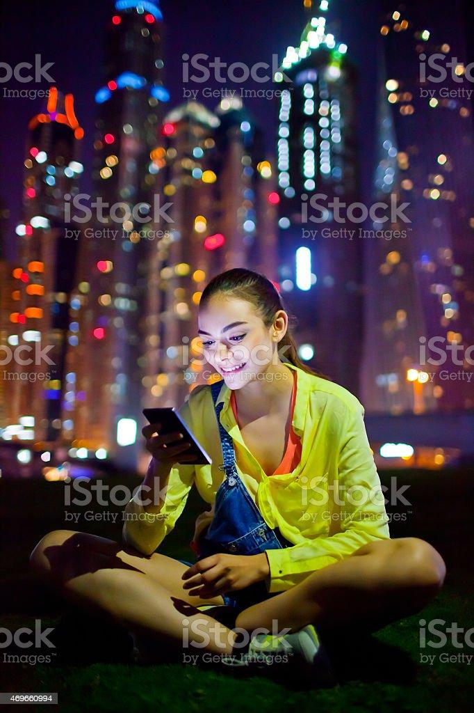 Woman texting on the smart phone in Dubai Marina stock photo