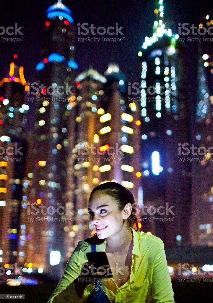 Woman texting on the smart phone in Dubai Marina. stock photo