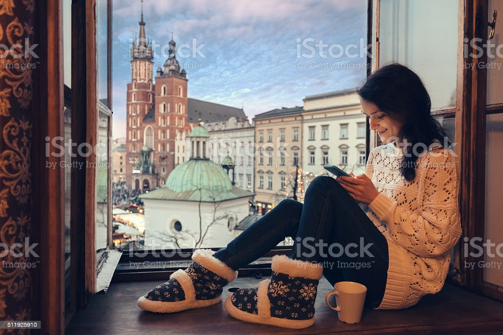 Woman texting on the window sill in Krakow stock photo
