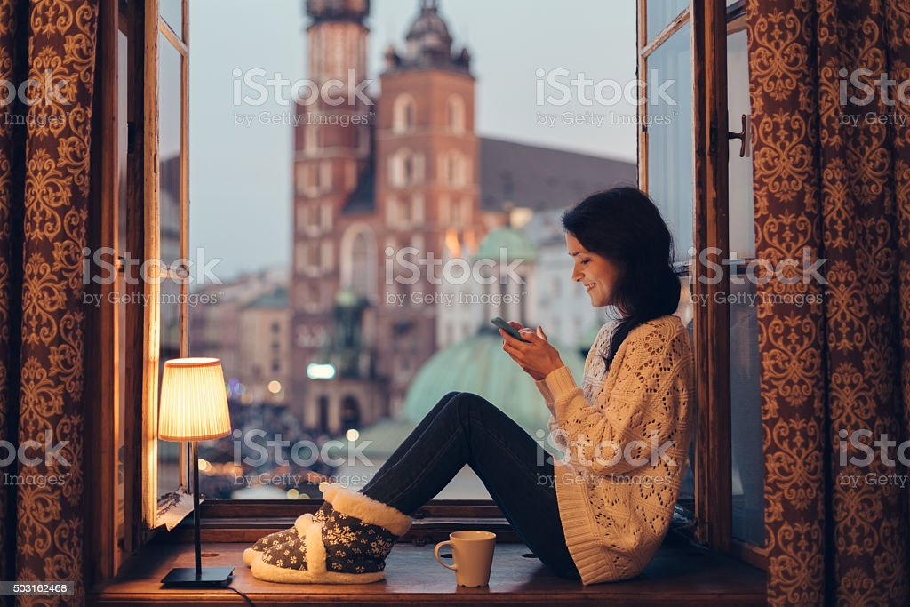 Woman texting on the window sill stock photo