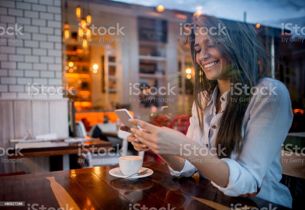 Woman texting while drinking coffee at cafe stock photo