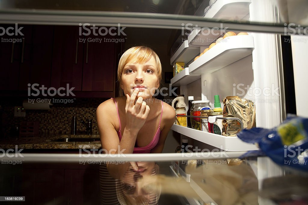 Woman thinking about her food choice inside refregirator stock photo