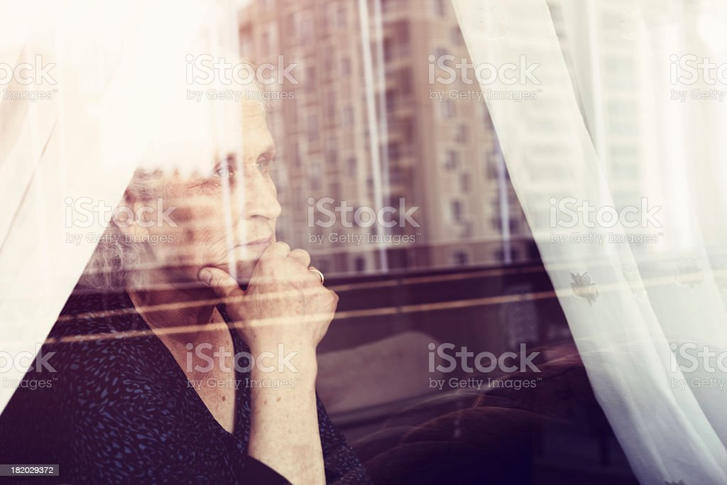 A woman thinking deeply whilst looking out of a window stock photo