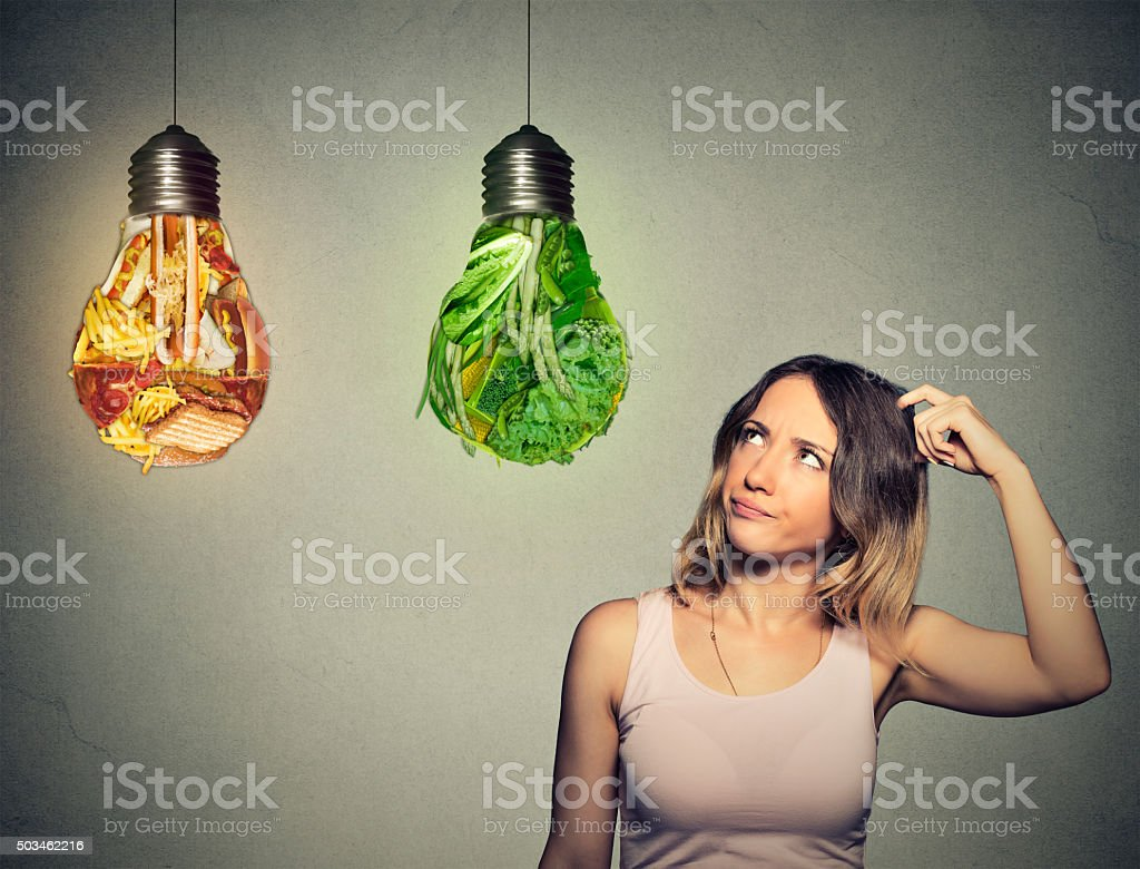 woman thinking looking up at junk food green vegetables stock photo