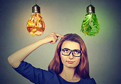 Woman thinking looking up at junk food vegetables lightbulbs