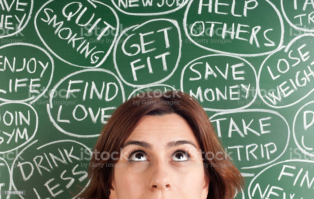A woman thinking of different New Years resolutions stock photo