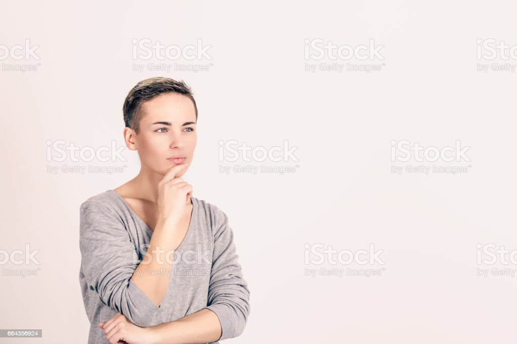 Woman thinking. Portrait close up of happy beautiful young woman thinking looking away, up isolated grey wall background with copy space. Human face expressions, emotions feelings, body language stock photo