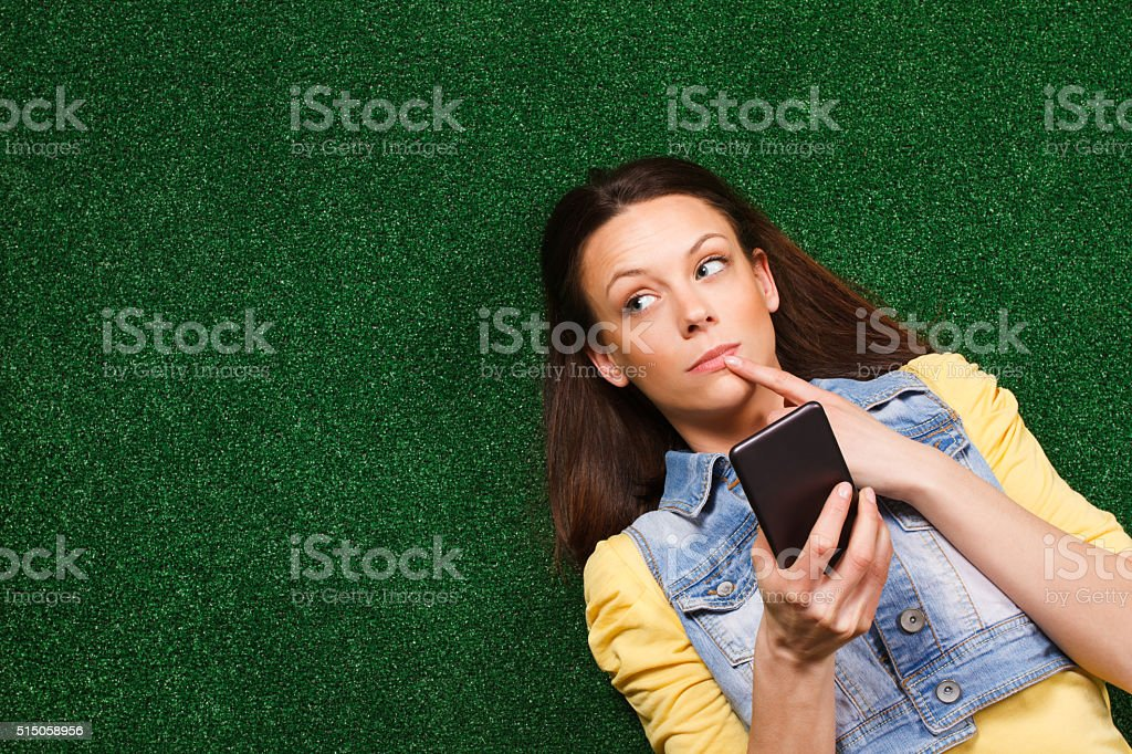 Woman thinking while texting message stock photo