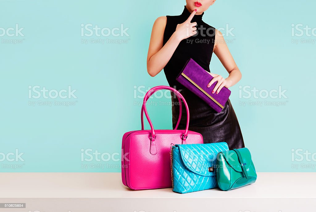 Woman thinking with many colorful bags. Shopping. Fashion image. stock photo