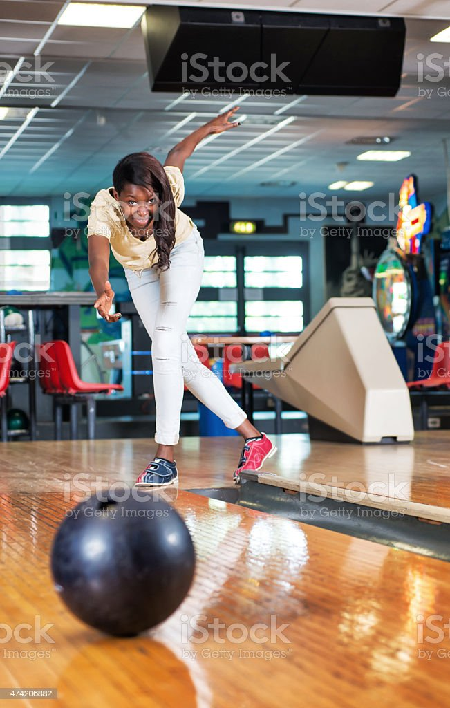 Woman throwing a bowling ball. stock photo