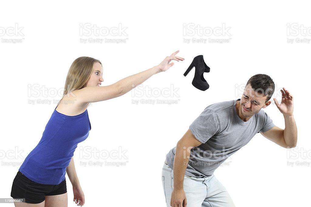 Woman throwing a heel shoe to man stock photo